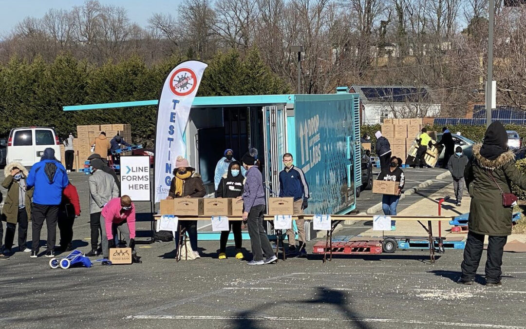 People line up in a church parking lot receiving boxes of food and COVID-19 tests.